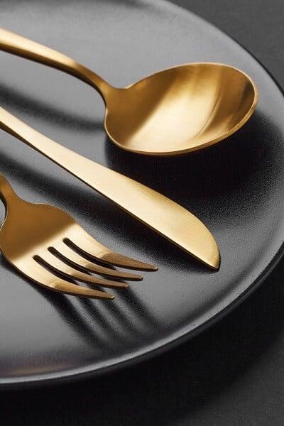 Guldbestik på sort tallerken forberedt til Gaudium barnedåbsmenu